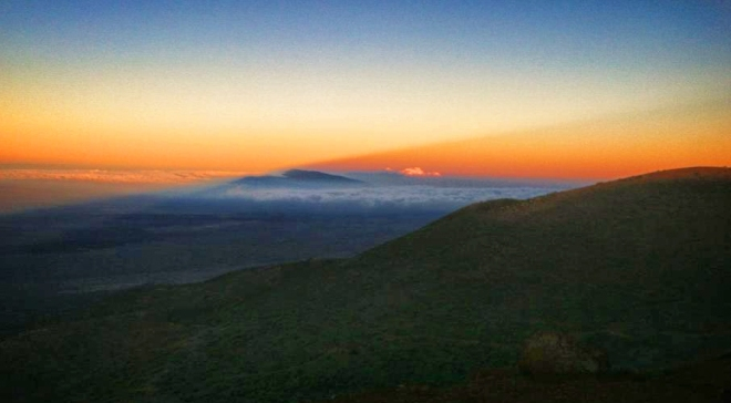 Turning back during sunset. Mt. Hualalai is seen in the distance as a dark blue peak extending above the cloud layer. The diagonal line seen starting in the dark blue shadow on the lefthand side and extending into the red-orange sky is the shadow of Mauna Kea.