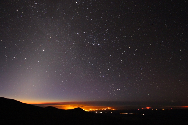 Pre-twilight overlooking Hilo. Zodiacal light is seen extending diagonally from the lower left of the frame. The Milky Way intersects the zodiacal light, extending diagonally from the right.