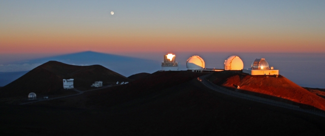 Sunrise over Mauna Kea. Four large telescopes from left to right: Subaru, Keck I and II, IRTF. Lower left are the telescopes that make up submillimeter valley. The dark blue peak in the background is the shadow of Mauna Kea. On full moon nights, the moon sets just as the sun rises.