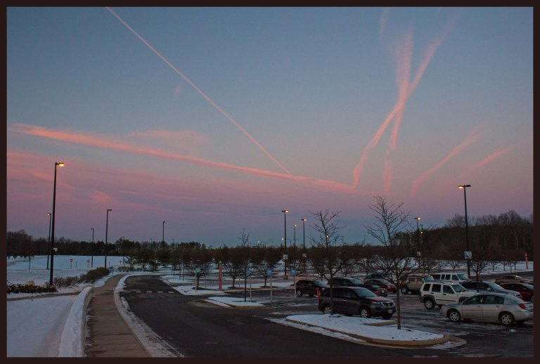 Contrails from planes at Dulles International Airport create a beautiful sunset
