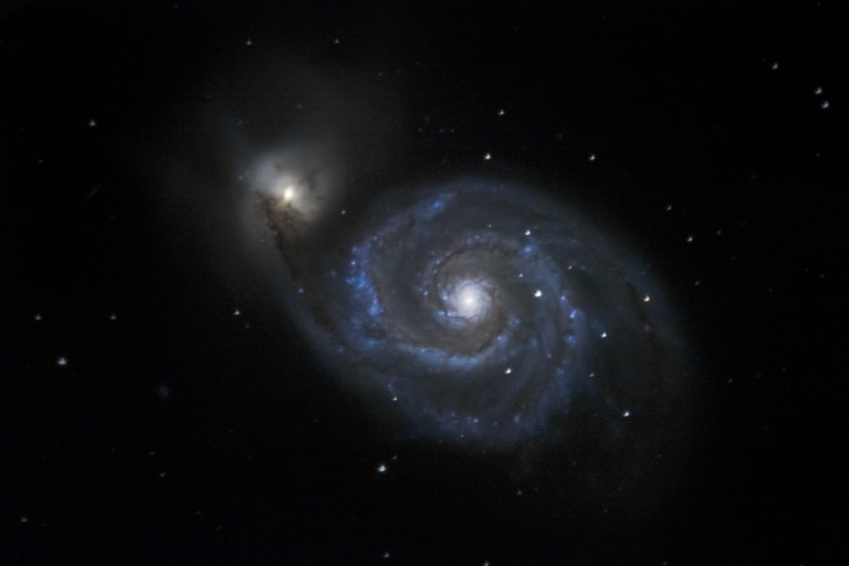 M51 - The Whirlpool Galaxy A face-on spiral galaxy currently undergoing a collision with its dwarf galaxy companion to the upper left.