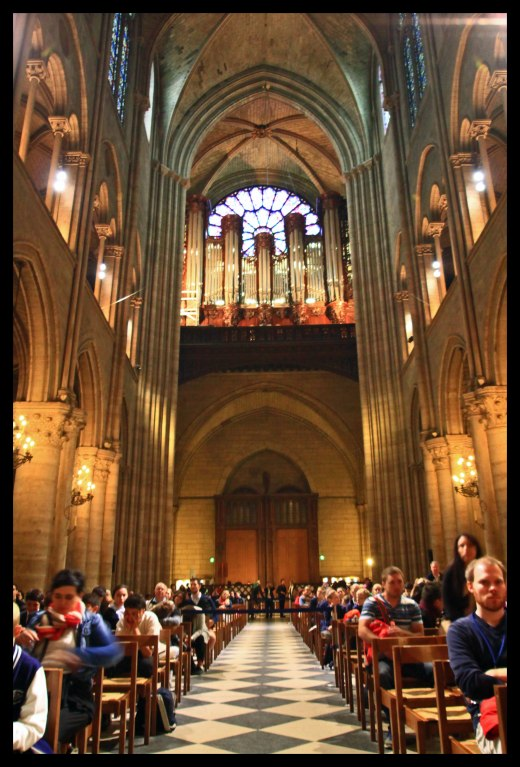 "Looking toward the back of the cathedral, the largest organ in France (the ""great organ"") can be seen beneath the stained glass window."