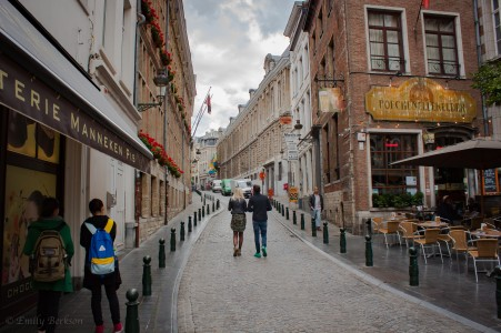 A couple walking the cobbled stones of Brussels on a bleary day.